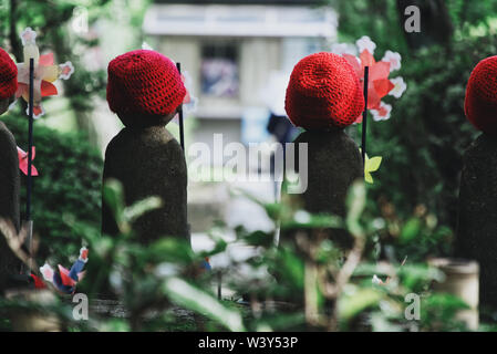 picture showing jizo child statues from behind at the zojoji temple in tokyo, back of little monk statues - Stock Photo