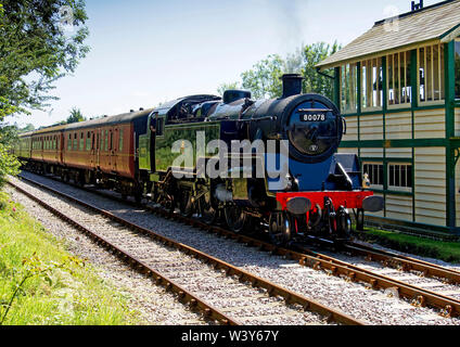 British Railways Standard Class 4 tank locomotive passes Hardingham signal box on the Mid-Norfolk Railway during the 2019 steam gala. - Stock Photo