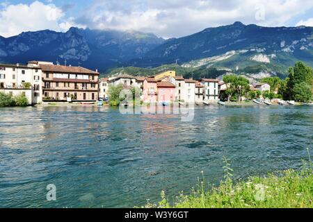 Panoramic view to Lecco Pescarenico fisherman district and the Adda river flowing in a sunny summer day with the Resegone mountain above them. - Stock Photo