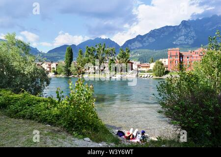 Lecco/Italy - July 10, 2014: Couple of tourist relaxing on the riverbank of Adda looking at Lecco Pescarenico fisherman district with mountains above. - Stock Photo