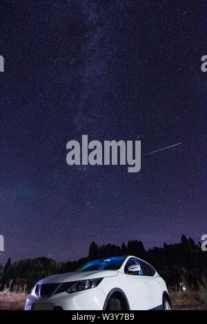 Stars and Milky Way with a shooting star above a white car in beautiful night sky - Stock Photo