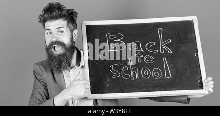Teacher bearded man holds blackboard with inscription back to school blue background. Beginning of new school year gives us new opportunities. Teacher informs about school year beginning. - Stock Photo