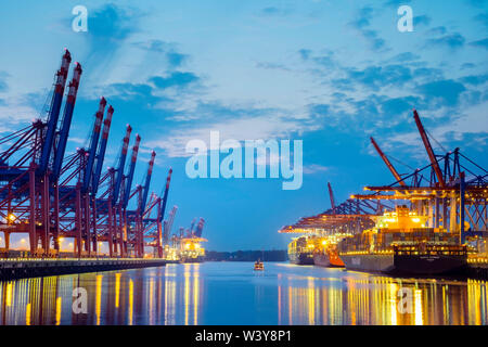 Cargo ships being loaded at Burchardkai in Hamburg Harbor at night, Waltershofer Hafen, Hamburg, Germany - Stock Photo