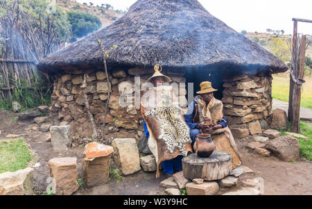 Basotho cultural village rural scene with two black African men dressed in traditional animal skins or hides outside a stone thatch rondawel or hut - Stock Photo
