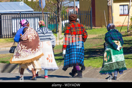 four black African women of Basotho origin wrapped up in traditional style blankets walk in a street in Clarens, Orange Free State, South Africa - Stock Photo