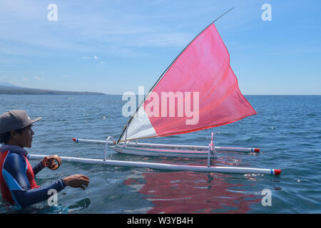 A young Indonesian stands in the sea and prepares a model ship for the competition. Small wooden sailboat with red-white sail and bamboo floats. - Stock Photo