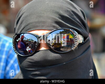 Fully covered Indian Muslima wears a black niqab and hides her eyes behind mirrored sunglasses. - Stock Photo