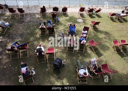 (190718) -- PARIS, July 18, 2019 (Xinhua) -- People rest during the Paris Plage at the banks of River Seine, in Paris, France, July 17, 2019. The annual Paris Plage (Paris beach) event is held from July 6 to Sept. 1, 2019. (Xinhua/Gao Jing) - Stock Photo