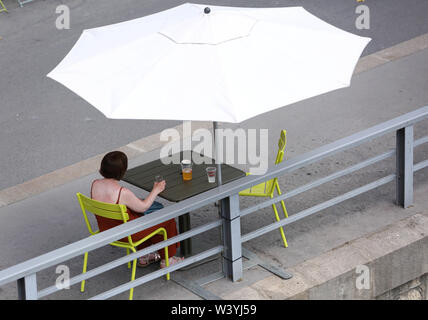 (190718) -- PARIS, July 18, 2019 (Xinhua) -- A woman rests during the Paris Plage at the banks of River Seine, in Paris, France, July 17, 2019. The annual Paris Plage (Paris beach) event is held from July 6 to Sept. 1, 2019. (Xinhua/Gao Jing) - Stock Photo