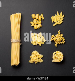 Assorted types of pasta on black background. Top view. Various forms of pasta. - Stock Photo