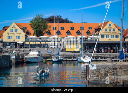 Svaneke, Denmark. 28th June, 2019. View from the harbour to Svaneke, a small town at the northeastern edge of the Danish Baltic Sea island Bornholm. Svaneke is the best preserved old town in Bornholm. The island Bornholm is, together with the offshore archipelago Ertholmene, Denmark's most eastern island. Thanks to its location, the island of Bornholm counts many hours of sunshine. Credit: Patrick Pleul/dpa-Zentralbild/ZB/dpa/Alamy Live News - Stock Photo