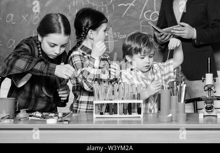chemistry lab. back to school. happy children teacher. kids in lab coat learning chemistry in school laboratory. making experiment in lab or chemical cabinet. Testing blood samples. - Stock Photo