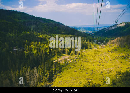 Summer mountain landscape with green tall dense trees, light green bright valley and cable car up to the mountains. Travel and vacation concept. - Stock Photo