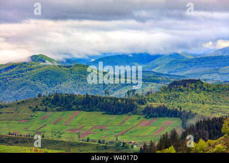 Rectangular land agricultural areas of local residents are located in a valley on a hillside against the backdrop of the picturesque landscape of the - Stock Photo