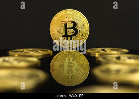 A mirror reflection of a big golden BTC coins. The coin of bitcoin is on a black table and black background. - Stock Photo