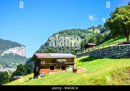 Beautiful mountain hut near Lauterbrunnen in Swiss Alps. Stunning Alpine landscape in summer season. Sunny day, green hills. Chalet in Switzerland. Swiss Alps. - Stock Photo