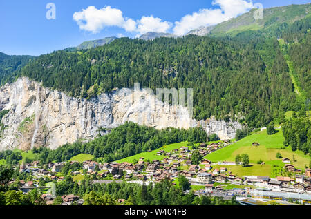 Amazing view of picturesque Swiss village Lauterbrunnen in summer from above. Famous Staubbach Falls. Swiss Alps. Switzerland landscape. Beautiful cityscape. Alpine. - Stock Photo