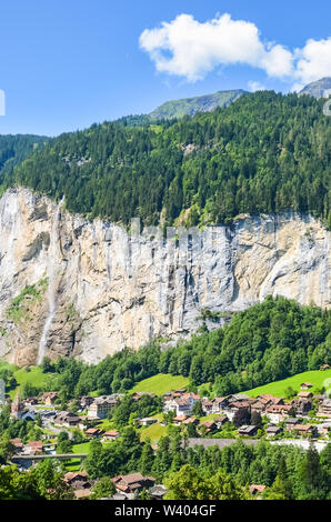 Lauterbrunnen, Switzerland photographed from above with famous Staubbach Falls. Summer Alpine landscape, Swiss Alps. Picturesque village. Rocks. - Stock Photo