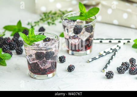 Cold summer berry drink with blackberries. Refreshing summer drink with syrup, blackberry and ice on light gray concrete background - Stock Photo