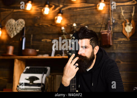 Connection through music. Man bearded musician enjoy evening with bass guitar, wooden background. Man with beard hugs neck of electric guitar. United - Stock Photo