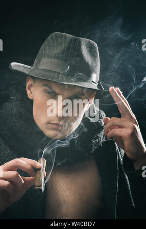Vintage detective concept. Man in coat, hat smoking cigar, dark background. Guy in old fashioned outfit looks mysterious with cigar and smoke. Macho o