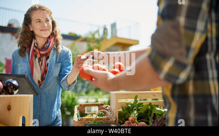 Friendly woman tending an organic vegetable stall at a farmer's market and selling fresh vegetables from the rooftop garden - Stock Photo