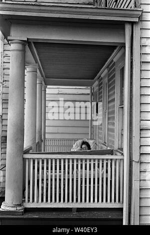 Old timber clad building house, wood cladding wooden boards, exterior outside woman asleep sleeping  on her house porch. New Brunswick, New Jersey. 1969, USA 60s US HOMER SYKES - Stock Photo