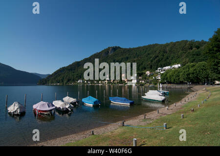 Beautiful view of many boats lined at the shore of Caslano Village lakeside. This Village is a famous tourist spot in the region of Lugano in the Cant - Stock Photo