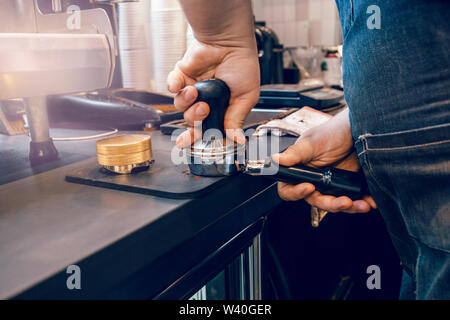 Closeup of barista hands using tamper to press ground coffee into portafilter to make espresso hot drink. Small local business work in cafe. - Stock Photo