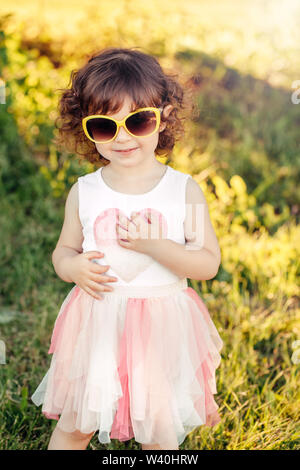 Young little girl posing. Portrait of cute adorable stylish Caucasian child in pink dress and yellow sunglasses outdoor in park at sunset on summer da - Stock Photo