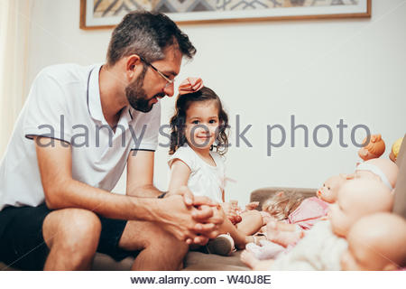 Father and daughter playing doll in living room - Stock Photo