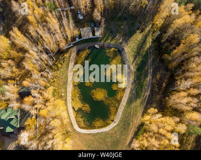 Small artificial reservoir pond for fishing with boat surrounded by golden autumn foret trees and cottage houses. Aerial drone view from above. - Stock Photo