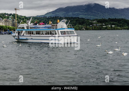 A view of beautiful lake Lucerne in Lucerne, Switzerland with view of old town and boats on a cloudy morning - Stock Photo