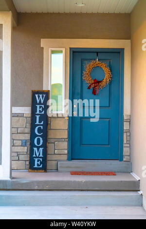 Golden wreath on the blue front door of a house with concrete and stone wall. A wooden Welcome sign is placed in front of the sidelight. - Stock Photo