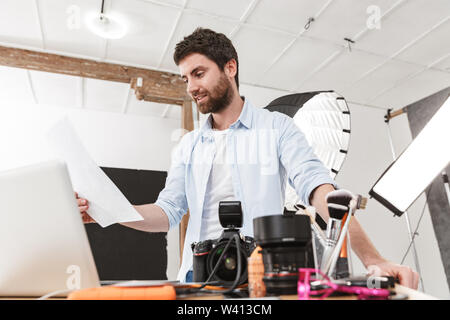 Portrait of creative brunette photographer man using laptop while shooting model with professional camera and softbox in studio - Stock Photo