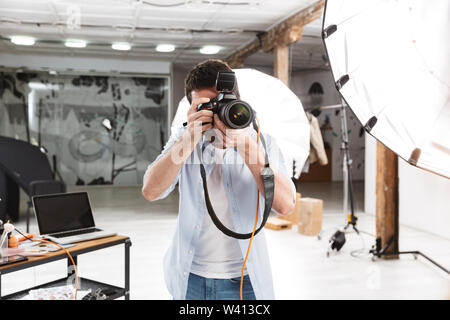 Portrait of young brunette photographer man shooting model with professional camera and softbox in studio - Stock Photo