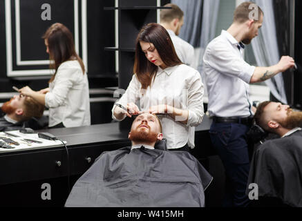Confident mans visiting hairstylists in barber shop. - Stock Photo