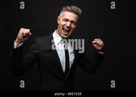 Confident attractive businessman wearing suit standing isolated over black background, celebrating success - Stock Photo