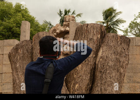 Hampi, India July 9, 2019 : Tourist trying to catpure Ugra Narsimha or Lakshmi Narsimha at Hampi. The man-lion avatar of Lord Vishnu - seated in a yog - Stock Photo