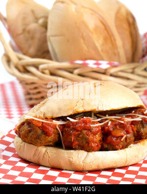 Delicious Italian meatball with marinara sauce sub sandwich, with a basket of crusty rolls in the background - Stock Photo