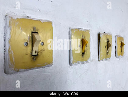 Four subjects electricians in the room. Vintage switch and light switch on the wall. - Stock Photo