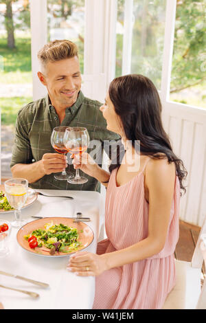 Dark-haired wife wearing pink dress drinking wine with husband - Stock Photo