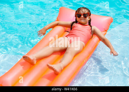 Funny girl wearing sunglasses chilling on air mattress in the pool - Stock Photo