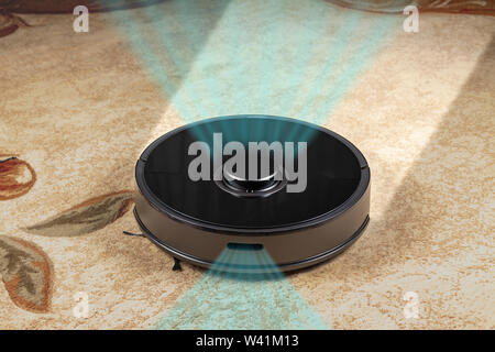The robot vacuum cleaner in the room cleans the carpet. - Stock Photo