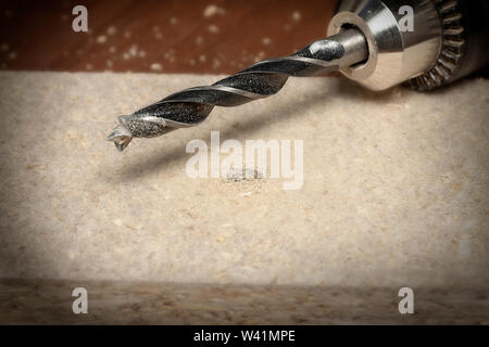 Steel boer drill a hole in a wooden board. Variety of carpentry tools and locksmith instruments close-up. Joinery work. - Stock Photo