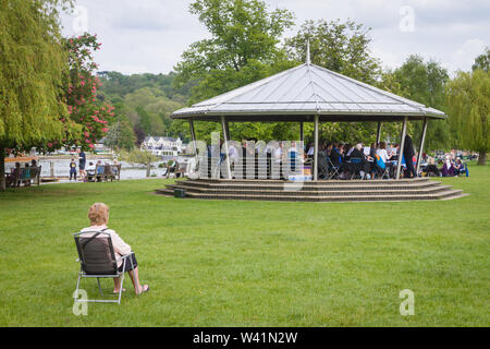 Sitting in the park at Mill Meadows, Henley-on-Thames, listening to the brass band play on the bandstand - Stock Photo
