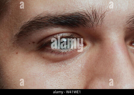 Close-up portrait of young man isolated on grey studio background. Caucasian male model's face and blue eye. Concept of men's health and beauty, self-care, body and skin care, medicine or phycology. - Stock Photo
