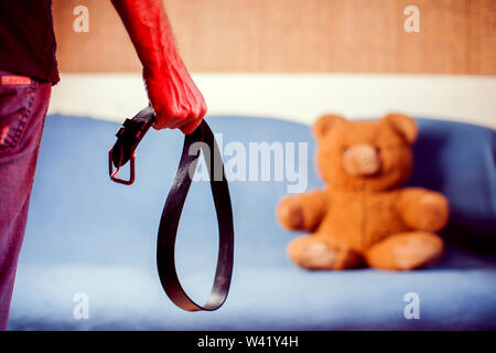 Domestic violence: male hand with belt on the background of toy bear. Abused child, aggression in the family concept - Stock Photo