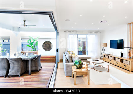 Modern living room attached to the patio and dining area including a plastic chairs and tables on the wooden floor outside near to the sofa and pillow - Stock Photo