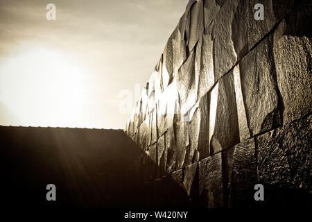 Dark and wet stone wall shines with direct sunlight hide in the clouds - Stock Photo